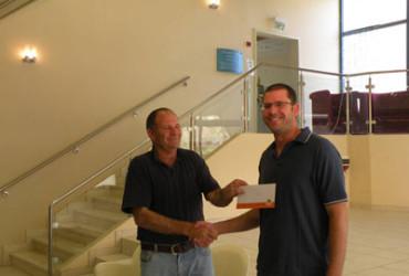 עזרא רבינס ראש המועצה האזורית ערבה תיכונה מעניק את המלגה לעודד קינן